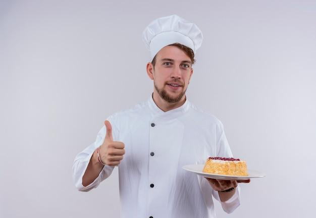 Ein fröhlicher junger bärtiger kochmann, der weiße kochuniform und hut hält, einen teller mit kuchen hält und daumen oben zeigt, während er auf eine weiße wand schaut