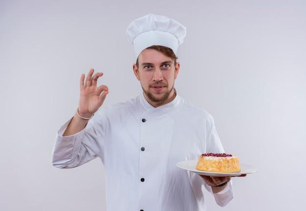 Ein fröhlicher junger bärtiger kochmann, der weiße kochuniform und hut hält, einen teller mit kuchen hält und leckere ok geste zeigt, während er auf eine weiße wand schaut