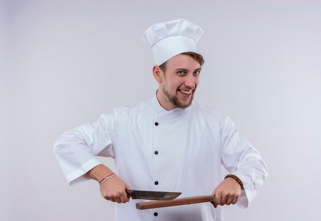 Ein fröhlicher junger bärtiger kochmann, der weiße kochuniform und hut hält messer über einem hölzernen küchenbrett trägt, während auf einer weißen wand schaut
