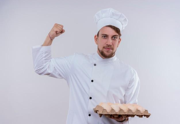 Ein fröhlicher junger bärtiger kochmann, der weiße kochuniform und hut trägt, hält einen karton von eiern mit geballter faust, während auf einer weißen wand betrachtet