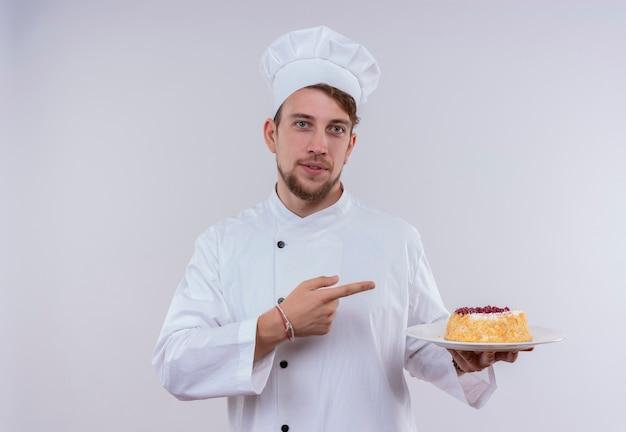 Ein fröhlicher junger bärtiger kochmann, der weiße kochuniform und hut trägt, zeigt auf einen teller mit kuchen mit zeigefinger, während auf einer weißen wand schauend