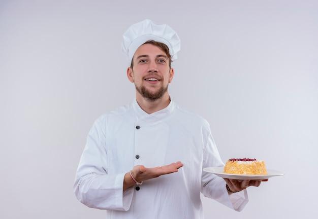 Ein fröhlicher junger bärtiger kochmann, der weiße kochuniform und hut trägt, zeigt einen teller mit kuchen, während auf einer weißen wand schauend