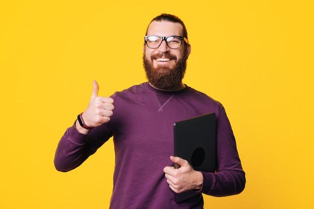 Ein fröhlicher junger bärtiger mann hält einen computer in der hand, der einen daumen nach oben zeigt und eine brille in der nähe einer gelben wand trägt