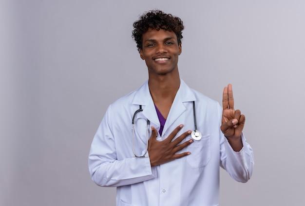 Ein fröhlicher junger gutaussehender dunkelhäutiger männlicher arzt mit lockigem haar, der einen weißen kittel mit stethoskop trägt und geste mit zwei fingern zeigt