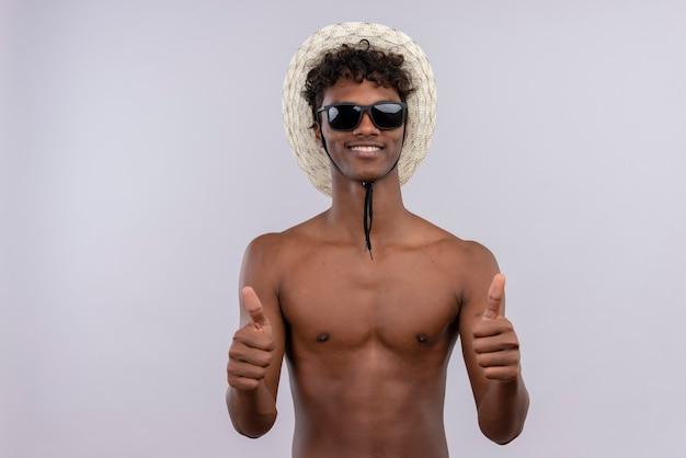 Ein fröhlicher junger gutaussehender dunkelhäutiger mann mit lockigem haar, sonnenhut und sonnenbrille, die dabei daumen hoch zeigt