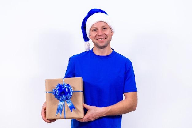 Ein fröhlicher kurier in blauer uniform und weihnachtsmütze hält eine geschenkbox mit schleife