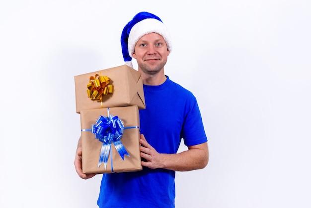 Ein fröhlicher kurier in blauer uniform und weihnachtsmütze hält zwei geschenkboxen mit schleifen