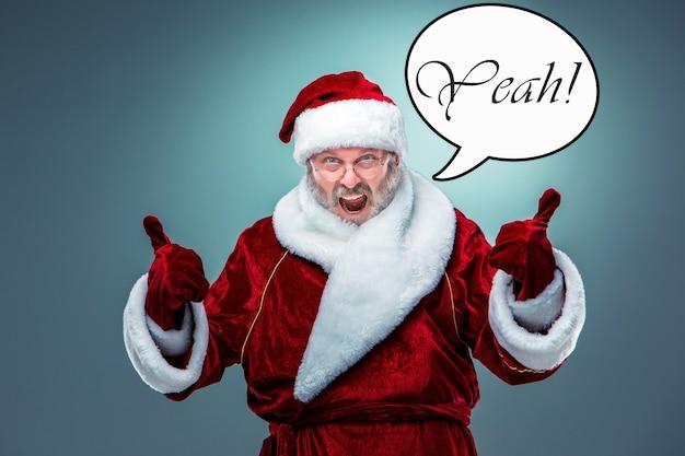 Ein fröhlicher, lächelnder weihnachtsmann mit brille mit grauem bart auf blauem grund