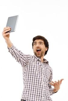 Ein fröhlicher mann, der die tablette hochhebt, fand wlan