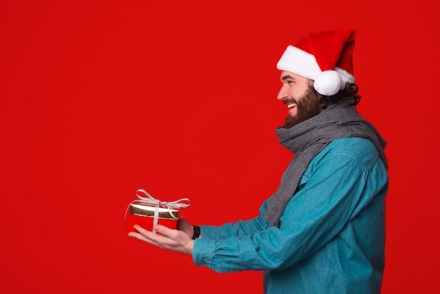 Ein fröhlicher mann, der eine weihnachtsmütze trägt, gibt ein verpacktes geschenk vorbei.