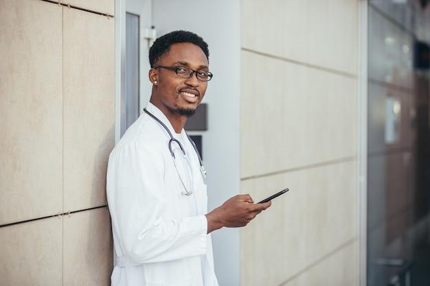Ein fröhlicher mann eines afroamerikanischen arztes in der nähe der klinik in einem weißen medizinischen kittel schaut in die kamera und hält ein mobiltelefon, um mit patienten zu sprechen, die in die kamera lächeln, und berichtet über gute nachrichten