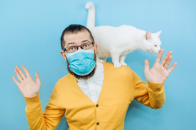 Ein fröhlicher mann in einer medizinischen maske mit einer weißen katze auf der schulter. pandemie covid 2019. haustier.