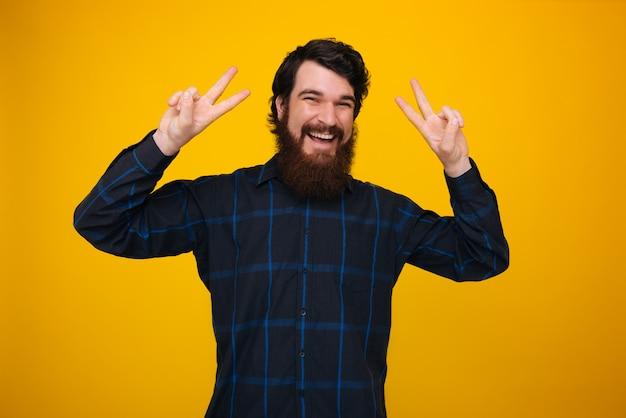 Ein fröhlicher mann mit bart und zahnigem lächeln, der friedensgeste über gelber wand tut