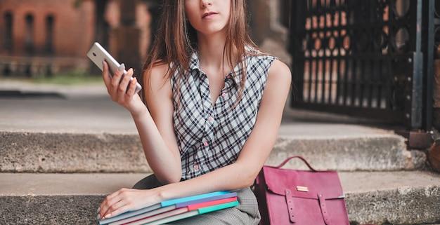 Ein fröhlicher student mit bunten notizbüchern und einem telefon sitzt auf den stufen in der nähe des campus und denkt über etwas nach