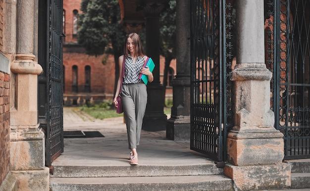 Ein fröhlicher student mit bunten notizbüchern und einer tasche läuft in der nähe des campus