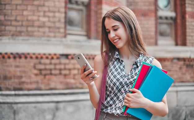 Ein fröhlicher student mit bunten notizbüchern wählt eine nachricht am telefon in der nähe der campuswände