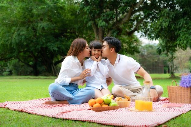 Ein fröhlicher urlaubspicknickmoment der asiatischen jugendlichen familie im park mit vater, mutter, die tochter küsst und lächelt, um glückliche urlaubszeit zu verbringen
