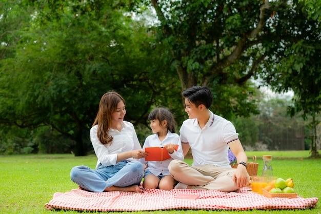 Ein fröhlicher urlaubspicknickmoment der asiatischen jugendlichen familie im park mit vater, mutter und tochter, die buch lesen und lächeln, um glückliche urlaubszeit zu verbringen