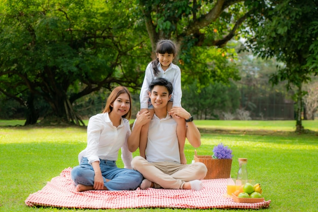 Ein fröhlicher urlaubspicknickmoment der asiatischen jugendlichen familie im park mit vater, mutter und tochter und lächeln, um glückliche ferienzeit zusammen im grünen garten mit obst und essen zusammen zu verbringen.