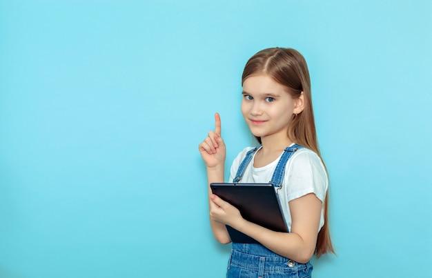 Ein fröhliches aufgeregtes mädchen zeigt mit dem finger auf den isolierten kopierraum