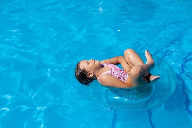 Ein fröhliches fünfjähriges mädchen, das mit gekreuzten beinen und geschlossenen augen auf einem blauen aufblasbaren kreis am meer schwebt...
