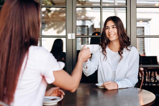 Ein fröhliches junges mädchen und eine freundin klirren an den bechern. sie sitzen im café. ansicht der ersten person.