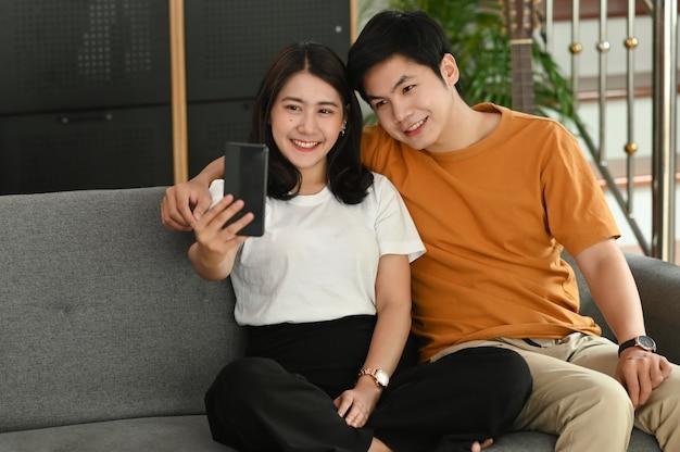 Ein fröhliches junges paar macht ein selfie-porträt auf dem sofa im wohnzimmer