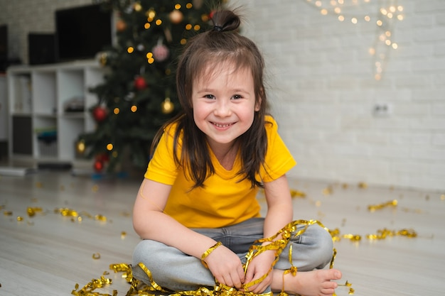 Ein fröhliches kind fängt lametta. ein heller kinderurlaub. ein kind in einem gelben t-shirt fängt eine serpentine
