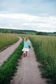 Ein fröhliches kind läuft mit einem strauß gänseblümchen in stiefeln