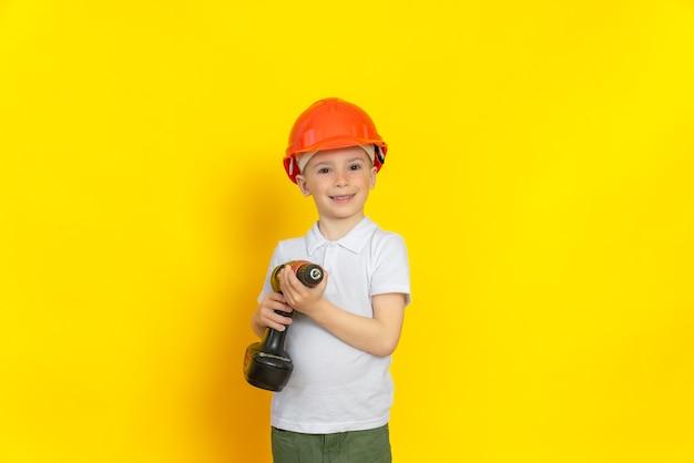 Ein fröhliches kind mit einem schraubenzieher in der hand in einem helm auf dem kopf