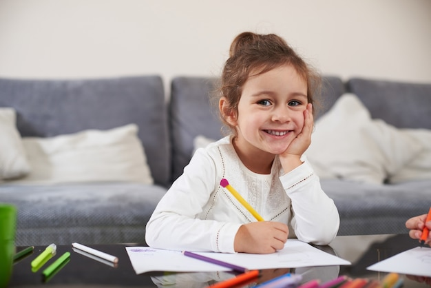 Ein fröhliches kleines mädchen, das am tisch sitzt, lächelt in die kamera, während es etwas auf papier schreibt. zu hause lernen