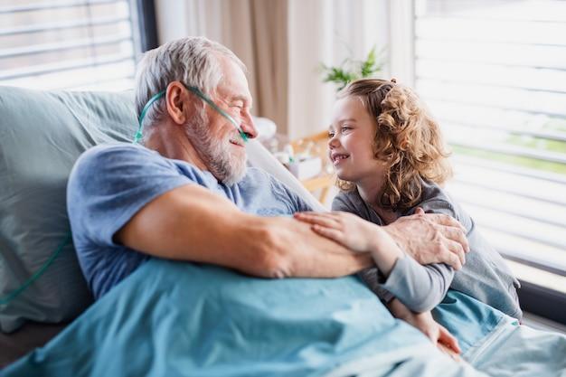 Ein fröhliches kleines mädchen, das den kranken großvater im bett im krankenzimmer besucht.