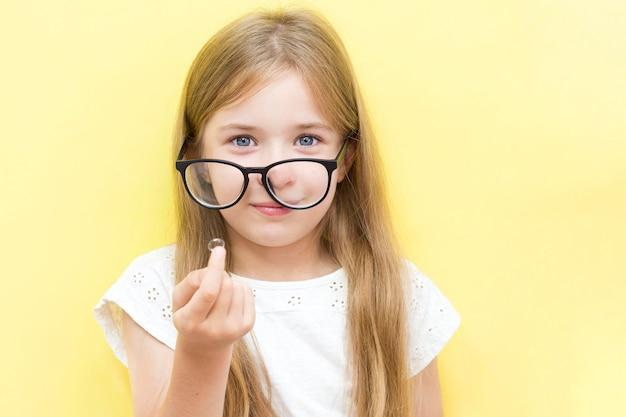Ein fröhliches mädchen auf gelbem hintergrund, das eine brille trägt und eine kontaktlinse hält. das konzept der sehprobleme bei schulkindern.