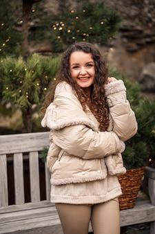Ein fröhliches mädchen geht zwischen den bäumen spazieren und lächelt, sie hat neujahrsstimmung