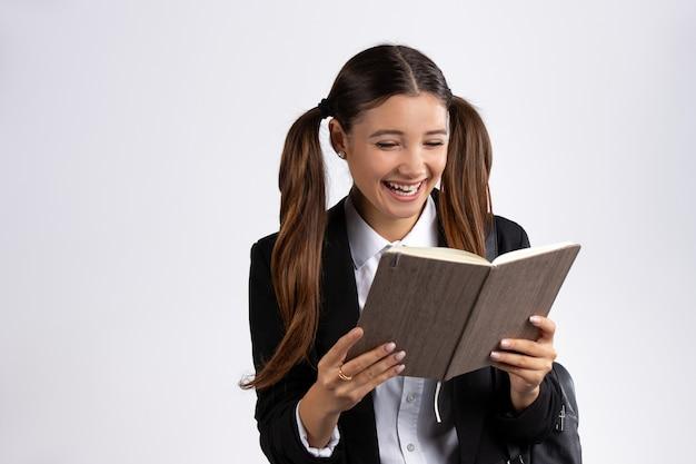 Ein fröhliches mädchen liest ein buch und lacht weiße wand leer