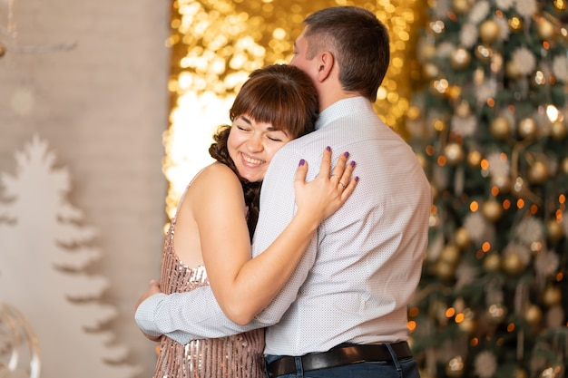 Ein fröhliches mädchen umarmt einen mann zwischen funkeln und gerlanden auf einer weihnachtsfeier