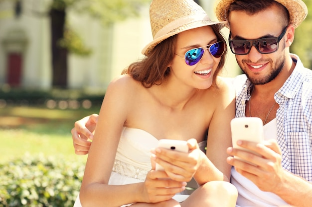 Ein fröhliches paar mit smartphones im park