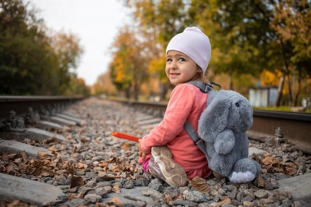 Ein fröhliches rowdymädchen sitzt auf den bahngleisen und lächelt verschmitzt. das kind hat etwas vor.