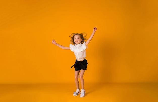 Ein fröhliches schulmädchen in uniform springt auf gelbem hintergrund mit einer kopie des raumes