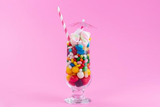 Ein frontansichtsglas mit süßigkeiten und konfekt auf rosa, süßer farbe regenbogen