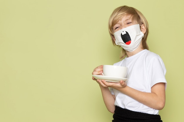 Ein frotn blick blondes kind entzückend süß süß in weißem t-shirt und lustiger maske, die tasse kaffee auf dem steinfarbenen schreibtisch hält