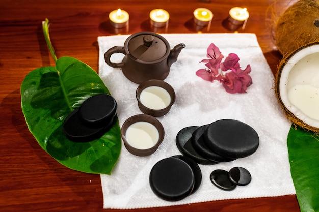 Ein frottiertuch mit einer teekanne aus ton und tassen für getränke mit milch, steine für die steintherapie, kerzen und eine mannolienblume