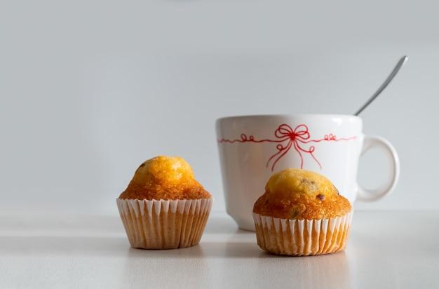 Ein frühstück zum start in den tag direkt im büro kaffee und zwei muffins mit schokolade