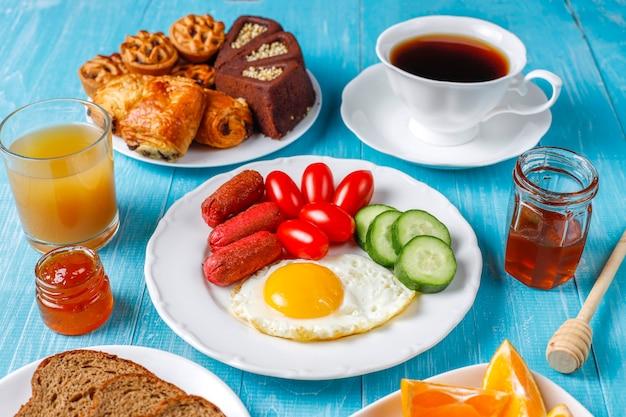 Ein frühstücksteller mit cocktailwürsten, spiegeleiern, kirschtomaten, süßigkeiten, früchten und einem glas pfirsichsaft. Kostenlose Fotos