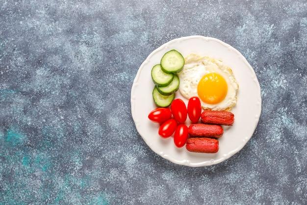 Ein frühstücksteller mit cocktailwürsten, spiegeleiern, kirschtomaten, süßigkeiten, früchten und einem glas pfirsichsaft.