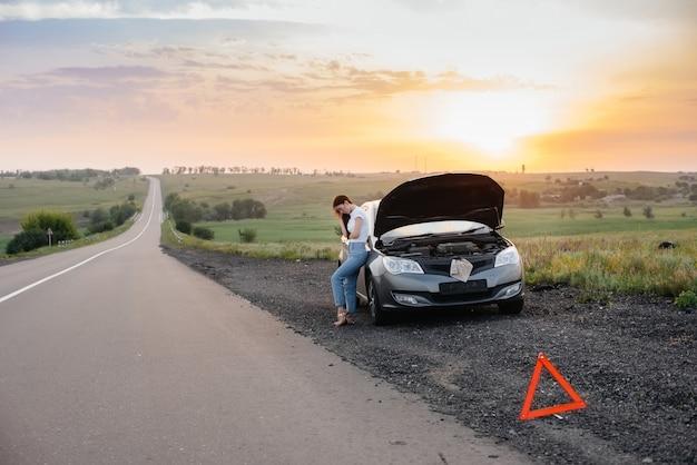 Ein frustriertes junges mädchen steht bei sonnenuntergang in der nähe eines kaputten autos mitten auf der autobahn. panne und reparatur des autos. warten auf hilfe.