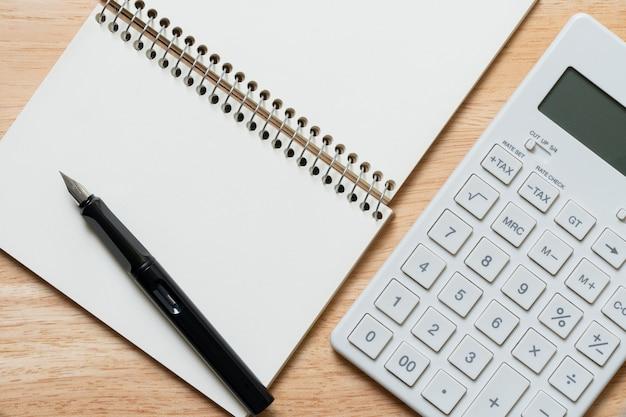 Ein füllfederhalter befindet sich auf einem notebook und einem taschenrechner. als hintergrund verwenden