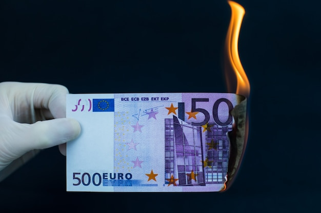 Ein fünfhundert-euro-schein brennt auf schwarzem hintergrund. weltkrisenkonzept.