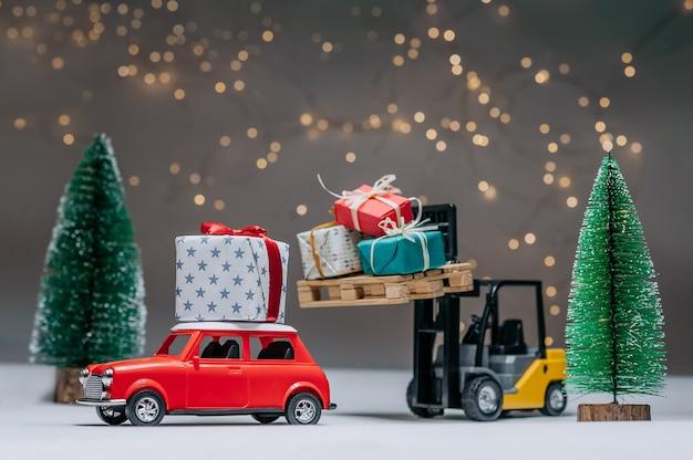 Ein gabelstapler lädt geschenke auf das rote auto. vor dem hintergrund grüner bäume und festlicher lichter. konzept zum thema weihnachten und neujahr.