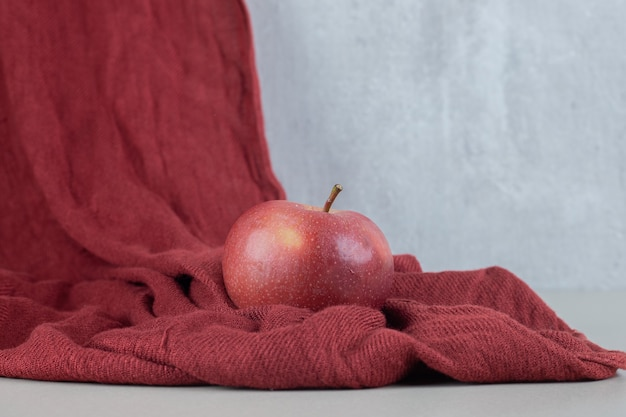 Ein ganzer roter frischer apfel auf einem tuch.